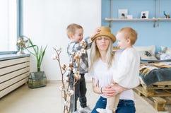 Junge und glückliche Mutter in einem Strohhut umarmt ihre zwei schönen Kinder Im Kinderraum zu Hause sitzen Stockfoto