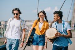 Junge und glückliche Straßenmusiker, die Instrumente tragen stockbilder