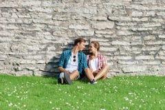 Junge und glückliches Paar, die im Park kühlen stockfotografie