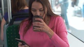 Junge und gl?ckliche Frau, die Smartphone beim Sitzen nahe dem Fenster in den ?ffentlichen Transportmitteln w?hrend der Reise ver stock footage