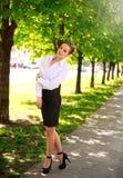 Junge und glückliche Geschäftsfrau, die in Stadtgrünpark geht Stockbilder