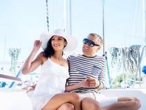 Junge und glückliches Paar, die auf Ferien auf einem Boot sich entspannen Lizenzfreies Stockfoto