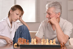 Junge und großväterliches Spielen stockfoto