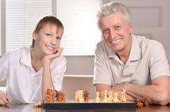 Junge und Großvater, die Schach spielen lizenzfreie stockfotografie