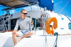 Junge und gutaussehender Mann auf einem Segelboot Stockbilder