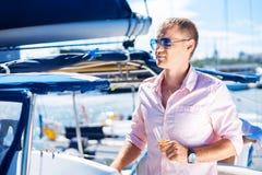 Junge und gutaussehender Mann mit Champagner auf einem Boot Stockfotos