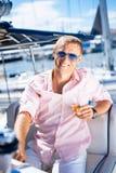 Junge und gutaussehender Mann mit Champagner auf einem Boot Stockfotografie