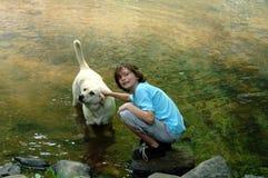 Junge und Hund, die im Fluss spielen Stockbilder