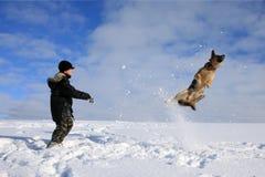 Junge und Hund, die im Schnee spielen Stockbild