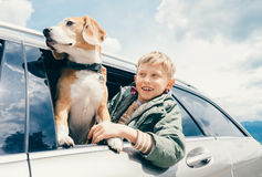 Junge und Hund schauen heraus vom Autofenster Stockbild