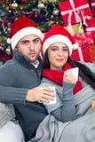 Junge und lächelnde Paare mit Sankt-Hut, der in x mas-Nacht sich entspannt Lizenzfreie Stockfotos