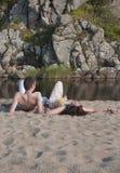 Junge und Mädchen auf dem Strand nahe dem Fluss, gegen die Felsen stockbilder
