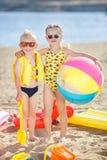Junge und Mädchen auf einem sandigen Strand mit einem großen aufblasbaren Ball Lizenzfreie Stockfotografie