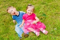 Junge und Mädchen auf Gras Lizenzfreie Stockbilder