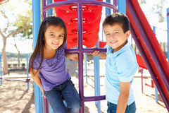 Junge und Mädchen auf kletterndem Rahmen im Park Stockbilder
