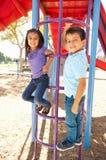 Junge und Mädchen auf kletterndem Rahmen im Park Lizenzfreie Stockbilder