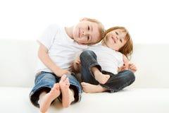 Junge und Mädchen auf Sofa Lizenzfreie Stockfotos