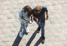 Junge und Mädchen betrachten Handy n die Straße lizenzfreie stockbilder