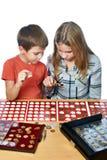 Junge und Mädchen betrachten Münzsammlung als lokalisiert stockbild