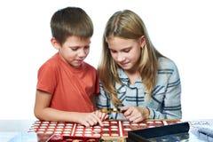 Junge und Mädchen betrachten Münzsammlung als lokalisiert lizenzfreies stockfoto
