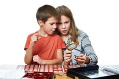 Junge und Mädchen betrachten Münzsammlung als lokalisiert lizenzfreies stockbild