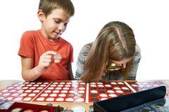 Junge und Mädchen betrachten Münzsammlung als lokalisiert lizenzfreie stockfotografie