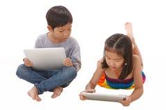 Junge und Mädchen, das Tablette beim Lügen auf dem Boden verwendet stockfotos