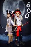 Junge und Mädchen in den Piratenkostümen Ein grimmiger Minireaper, der eine Sense anhält, steht auf einem Kalendertag, der glückl Stockfoto