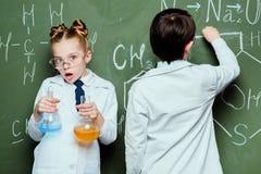 Junge und Mädchen in den weißen Mänteln, die mit Reagenzien in den Flaschen und in zeichnenden chemischen Formeln stehen stockbild