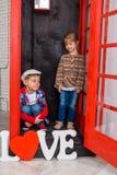 Junge und Mädchen in der Telefonzelle Stockbilder
