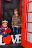 Junge und Mädchen in der Telefonzelle Lizenzfreie Stockfotos
