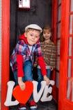 Junge und Mädchen in der Telefonzelle Stockfoto