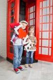 Junge und Mädchen in der Telefonzelle Lizenzfreies Stockfoto