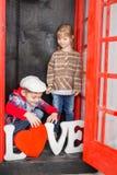 Junge und Mädchen in der Telefonzelle Stockbild