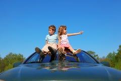 Junge und Mädchen, die auf Autodach auf Himmel sitzen stockbilder