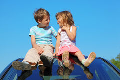 Junge und Mädchen, die auf Autodach auf Himmel sitzen stockfotografie