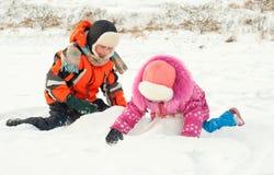 Junge und Mädchen, die auf dem Schnee spielen stockfotografie