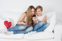 Junge und Mädchen, die auf der Couch mit Ihrem Telefon sitzen Lizenzfreies Stockfoto