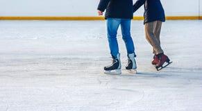 Junge und Mädchen, die auf die Eisbahn eislaufen Lizenzfreies Stockfoto
