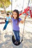 Junge und Mädchen, die auf Schwingen im Park spielen Stockfotografie