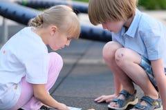 Junge und Mädchen, die auf seinen Hinterteilen sitzen Stockfotografie