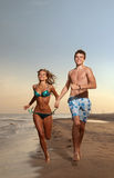 Junge und Mädchen, die auf Strand laufen Lizenzfreie Stockfotos