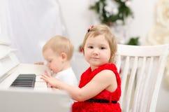 Junge und Mädchen, die auf weißem Klavier spielen lizenzfreie stockfotos