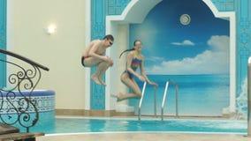 Junge und Mädchen, die in das Pool springen stock footage
