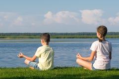 Junge und Mädchen, die draußen Yoga durch den See tun stockfotos