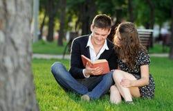 Junge und Mädchen, die ein Buch sitzt auf dem Gras liest Lizenzfreie Stockfotos