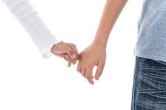 Junge und Mädchen, die ein Versprechen des kleinen Fingers auf Weiß machen Lizenzfreie Stockfotos