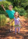 Junge und Mädchen, die in einem botanischen Garten gehen und wellenartig bewegen und lachen Stockfotos