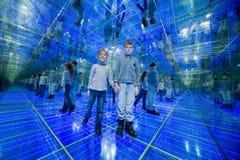 Junge und Mädchen, die in einem widergespiegelten Raum stehen Lizenzfreies Stockfoto