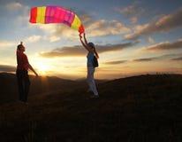 Junge und Mädchen, die einen Drachen auf Sonnenuntergang fliegen Stockbild